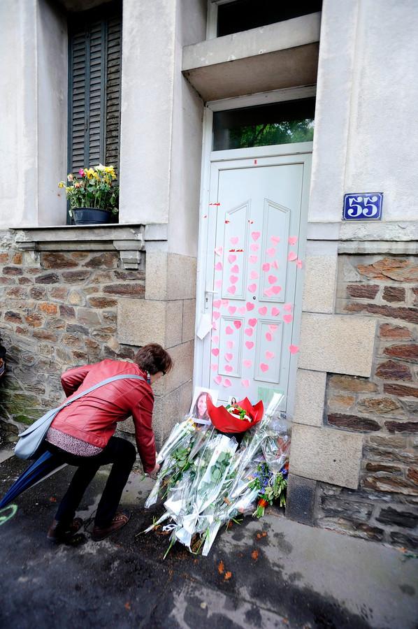 Een vrouw laat bloemen achter op de stoep van de 'moordwoning' in Nantes.