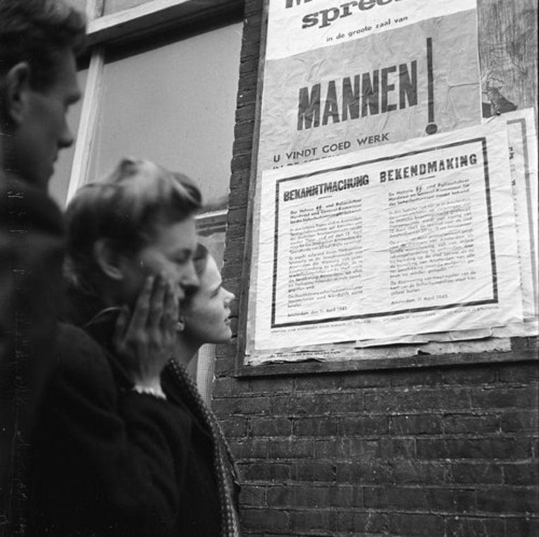 11 april 1945: in Amsterdam lezen inwoners in een muurkrant de bekendmaking van de Duitse bezetter dat een avondklok wordt ingesteld. Beeld Ad Windig