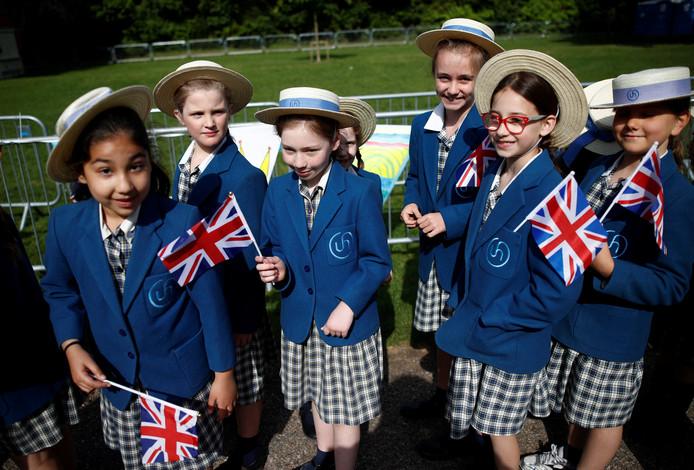 Een groep schoolkinderen uit Windsor neemt een kijkje langs de weg waar Harry en Meghan morgen langs komen. Foto Damir Sagolj