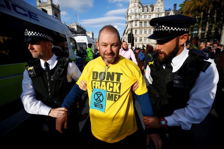 Politieagenten nemen een demonstrant mee tijdens een protest tegen fracking in 2018. Beeld null
