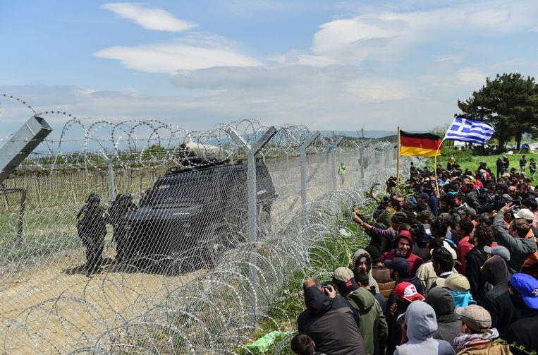 Vluchtelingen en migranten in Idomeni protesteren bij het hek dat de grensovergang met Macedonië markeert. Beeld null