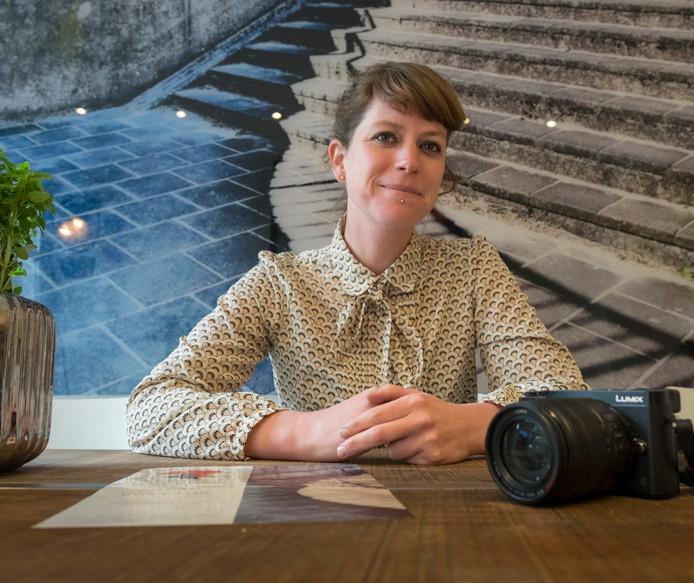 Sarah Kurvink met een van haar foto's op de achtergrond