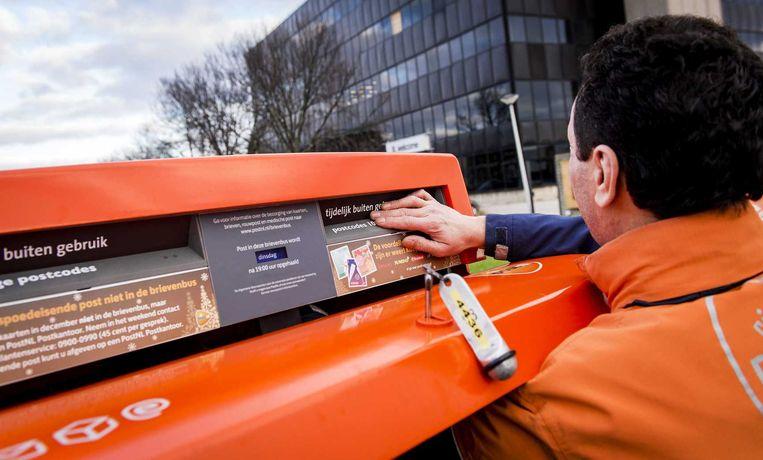 Een medewerker van PostNL sluit een brievenbus af om schade door vuurwerk te voorkomen. Beeld anp