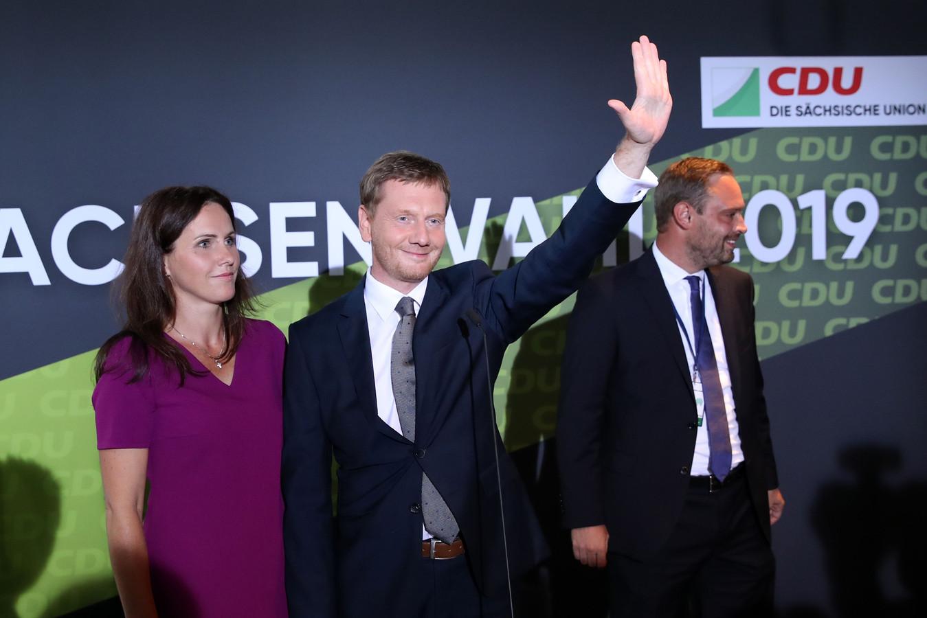 Michael Kretschmer (R), deelstaatpremier van Sachsen en topkandidaat van de CDU van Angela Merkel, met zijn echtgenote op het podium in Dresden na de bekendmaking van de exit polls.