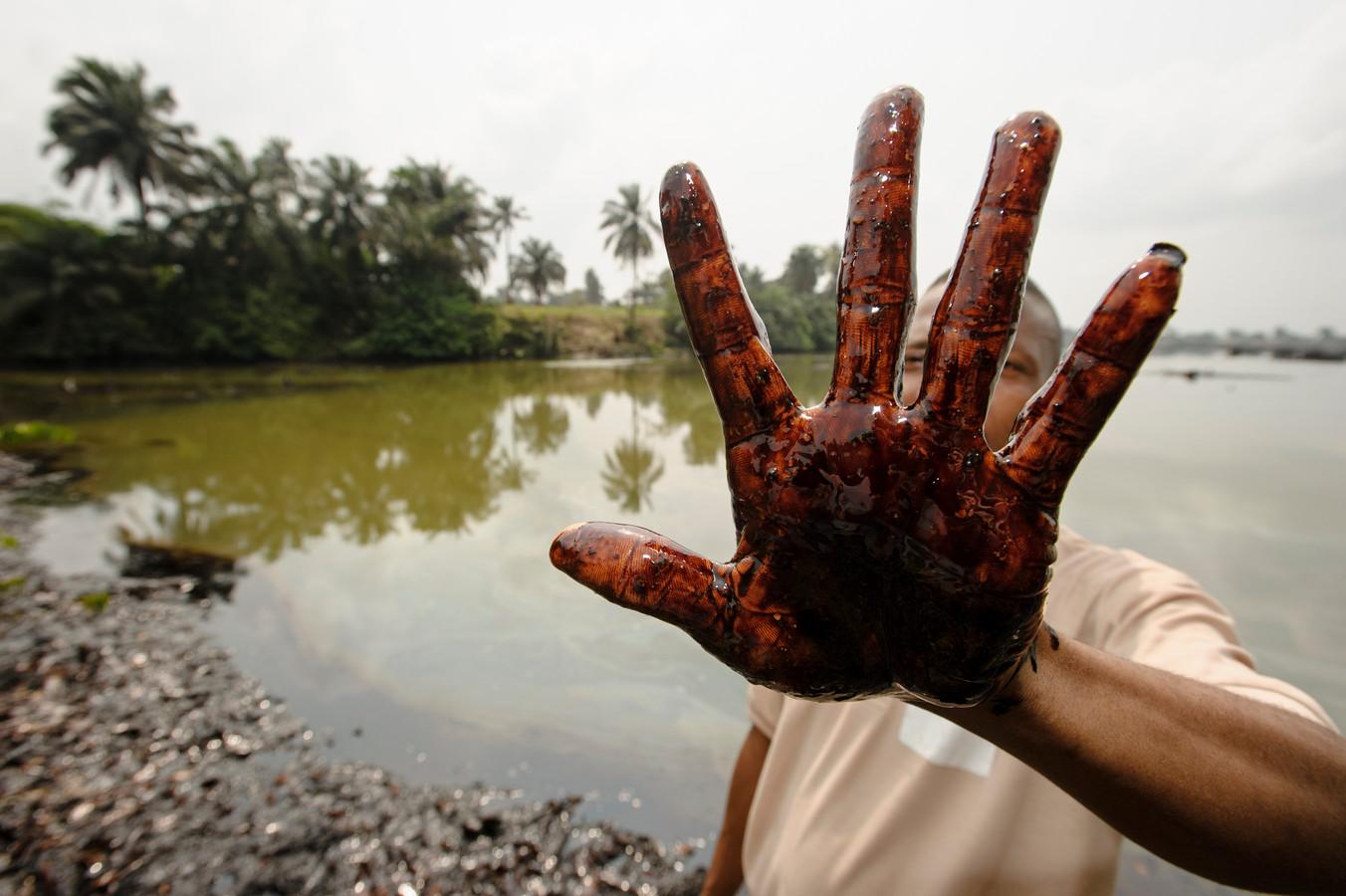 Een inwoner van Goi (Ogoniland, Nigeria) toont zijn hand die besmeurd is met ruwe olie. Oliewinning zorgde in het verleden voor veel schade in het gebied.