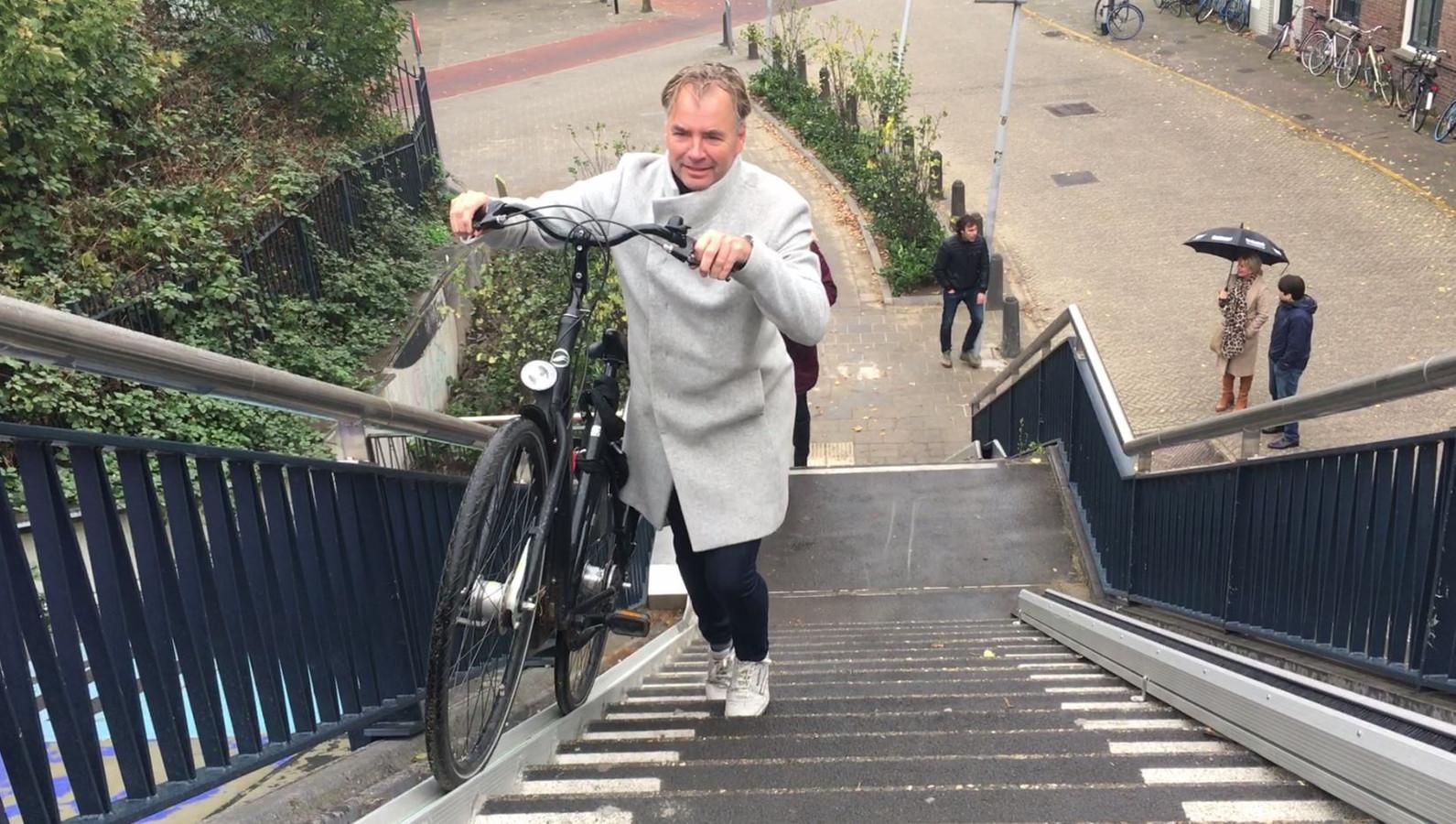 DNF-raadslid Jean-Paul Broeren neemt de nieuwe fietsgoot in gebruik naast de trap vanaf de Hezelpoort naar de Snelbinder.