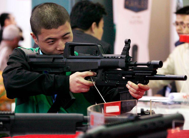 Een man houdt een geweer vast op een wapenbeurs in Peking, China. Beeld REUTERS