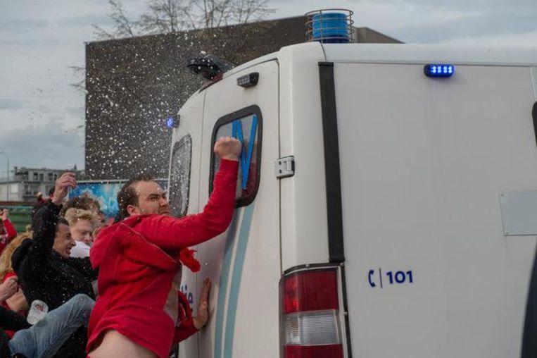 Een Antwerp-aanhanger koelt zijn woede op een politiewagen.