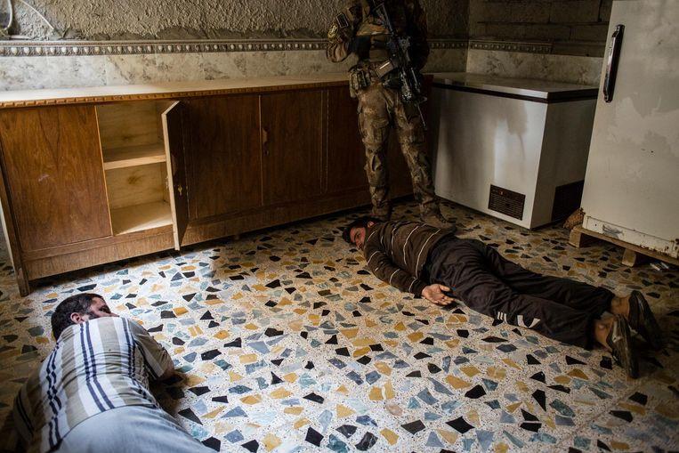 Een Iraakse soldaat heeft twee mannen aangehouden tijdens een zoektocht naar IS-strijders. Beeld null