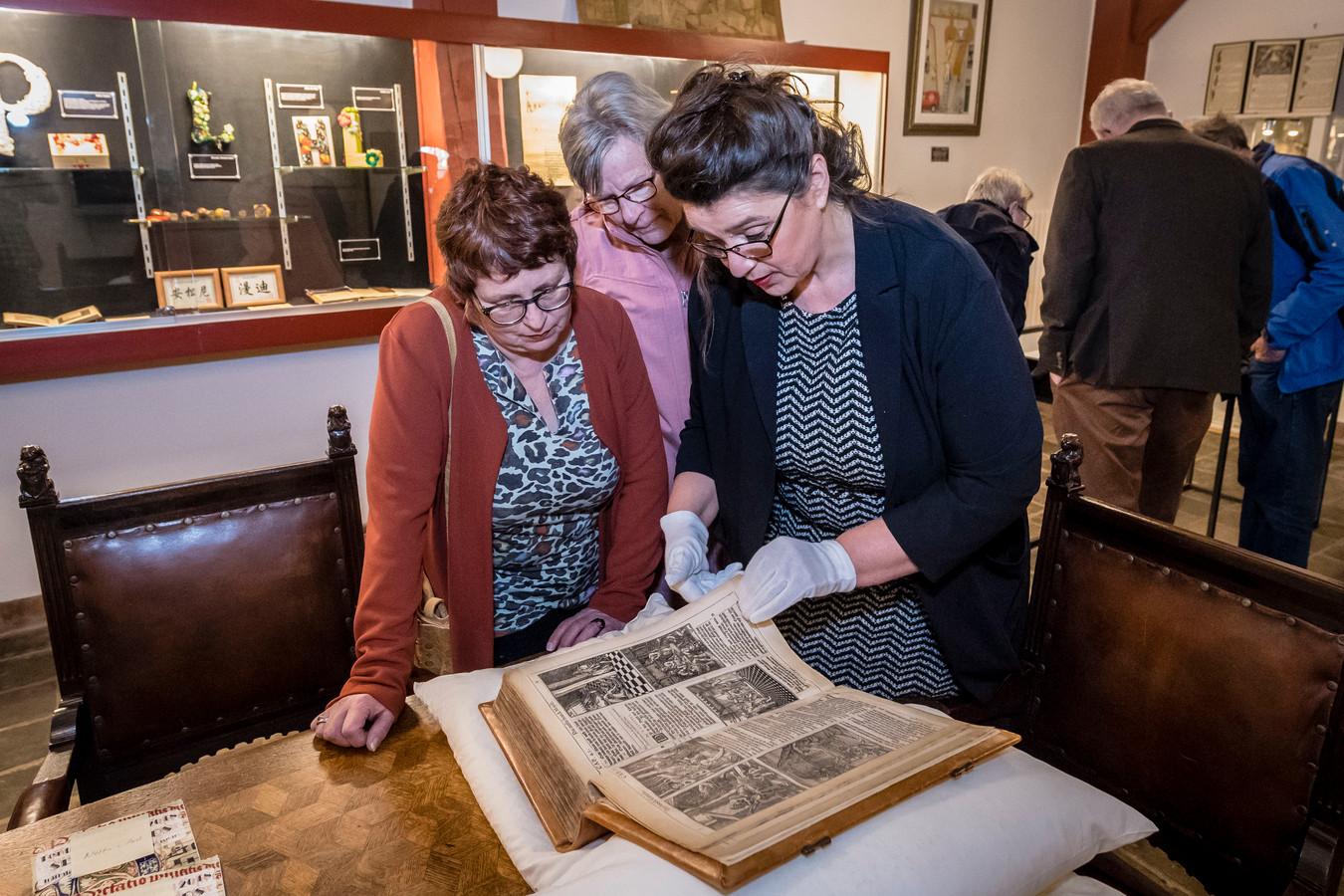 Een van de nieuwe suppoosten, Leonna Adank (rechts), laat bezoekers een boek uit 1657 zien.