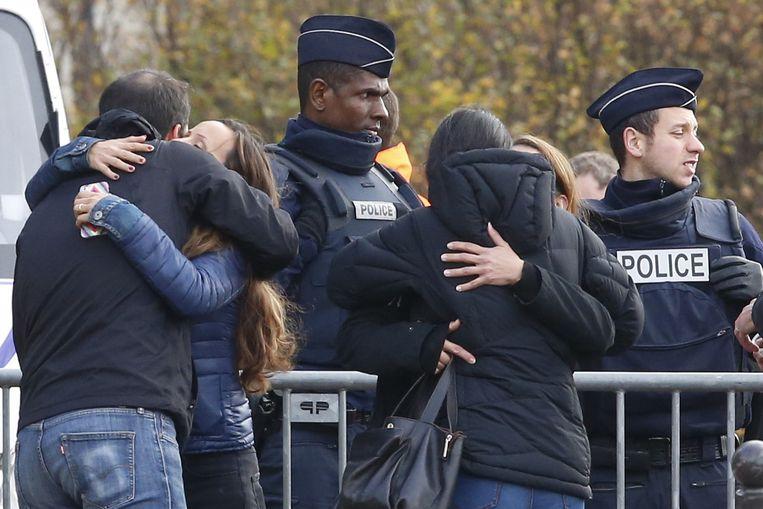 Parijs: jongeren omhelzen elkaar in verdriet bij een groot mortuarium in de Franse hoofdstad. Bij de aanslagen van vrijdag kwamen zeker 129 mensen om het leven. Beeld AP