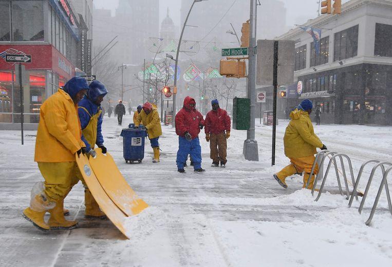 In de weer met grote sneeuwschoppen en stevig ingeduffeld proberen deze werkmannen de voetpaden in New York ijsvrij te krijgen.