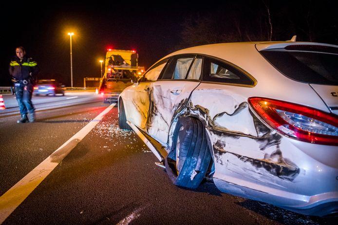 Vrachtwagen schampt auto met pech en belandt achter vangrails