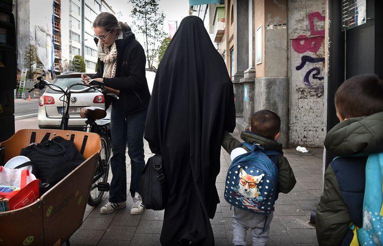 Een bakfietsmoeder en een moslima op straat in Borgerhout. Beeld Marcel van den Bergh