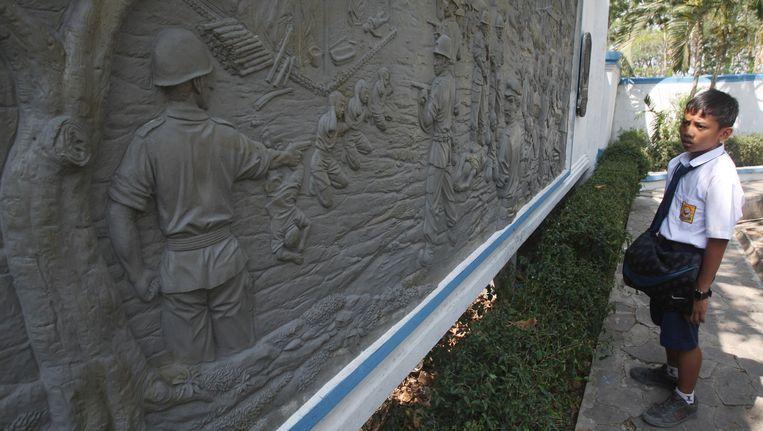 Een scholier in Rawagede kijkt naar het monument, welke is opgezet voor de slachtoffers van het bloedbad. Beeld AP
