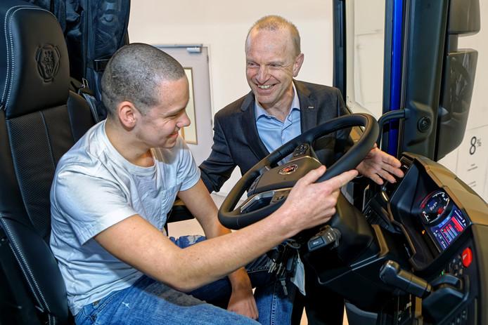 Daan Smeekens kruipt achter het stuur van een Scania-truck. Directeur Janko van der Baan geeft uitleg.