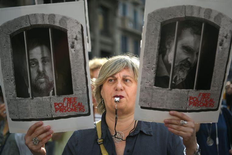 Een vrouw houdt tijdens een demonstratie portretten omhoog van de Catalaanse separatisten Oriol Junqueras en Jordi Cuixart.  Beeld null