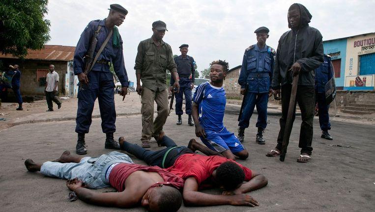 Agenten houden jongens aan in een wijk in Kinshasa die tot de oppositie zouden behoren. Beeld afp