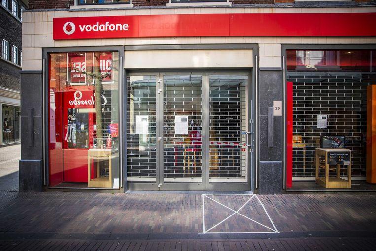 Strepen die aangeven dat klanten anderhalve meter afstand moeten bewaren in een winkelstraat in Haarlem.  Beeld ANP