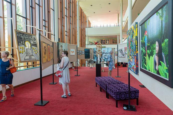 Kunstbeurs in het zomermuseum in theater de Spiegel. Bezoekers kijken rond.