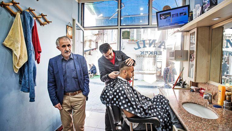 Syrische vluchtelingen aan het werk als kapper in de wijk Capa in Istanbul, waar veel Syriërs wonen Beeld Guus Dubbelman / de Volkskrant