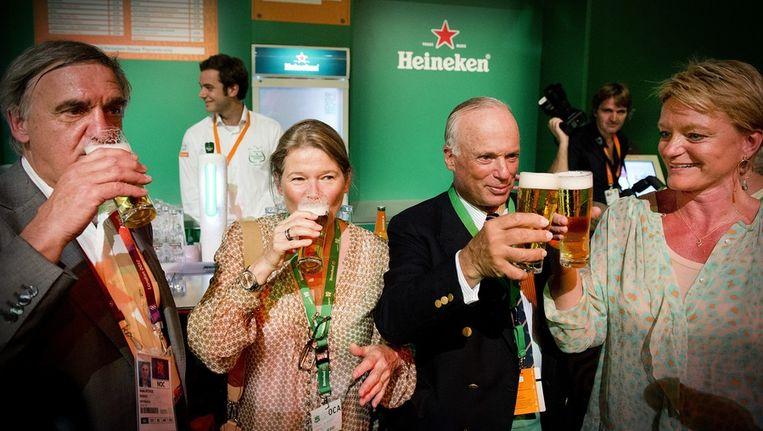 NOC*NSF voorzitter André Bolhuis (L), Charlene de Carvalho-Heineken (2eL), Michel de Carvalho (2eR) en Ellen van Langen toasten met een glas bier van het huismerk op de opening van het Holland Heineken House. Beeld anp