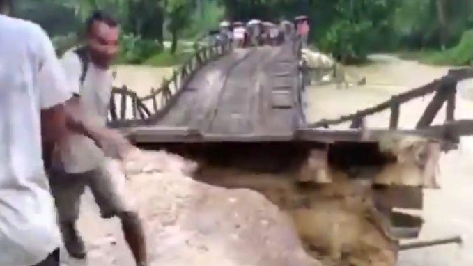 Paniek wanneer kolkende rivier brug meesleurt