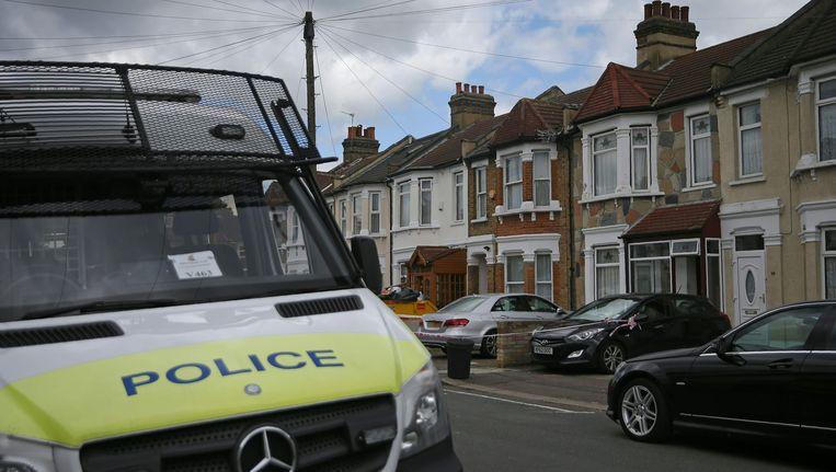 Politiebusje bij een huiszoeking net buiten Londen. Beeld afp