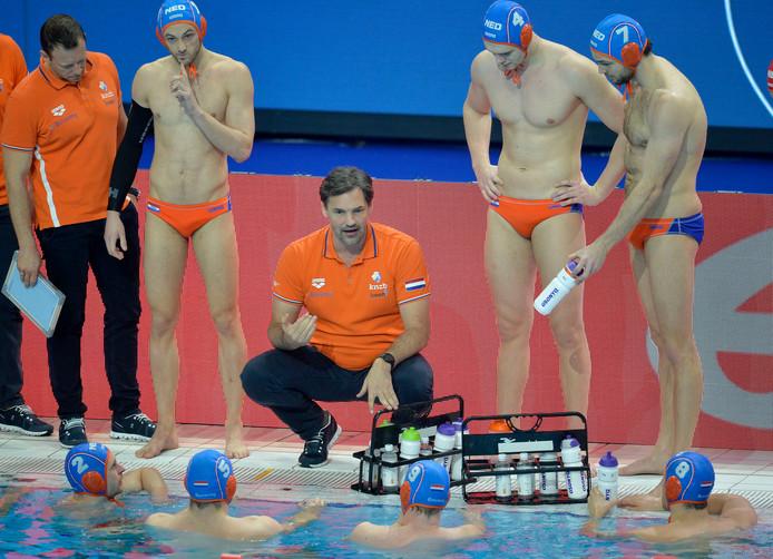 Bondscoach Harry van der Meer in gesprek met zijn spelers.