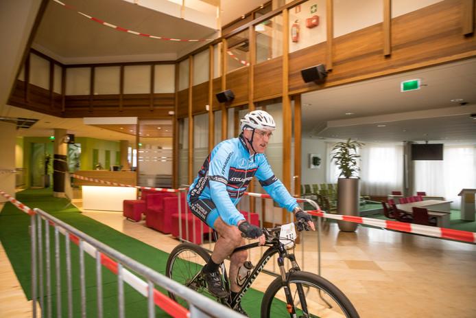 Bburgemeester Hoogendoorn op de fiets door zijn eigen werkplek, het gemeentehuis van Oldebroek.