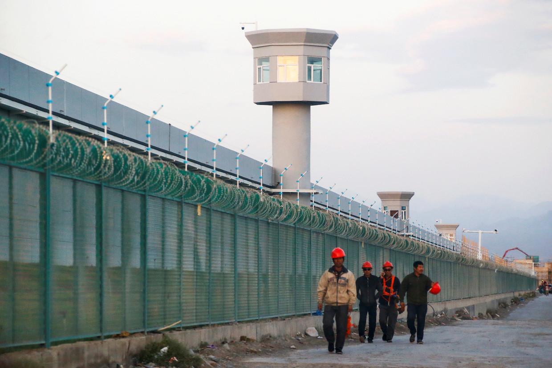Arbeiders lopen langs het hek van een heropvoedingskamp in de Chinese regio Xinjiang.