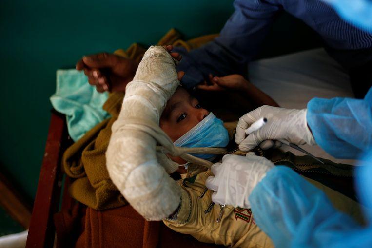 Een jongen  met difterie wordt onderzocht in Bangladesh.