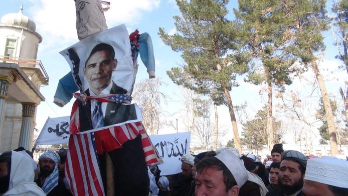 Afghanen dragen een poster van de Amerikaanse president Barack Obama tijdens een protest tegen de koranverbranding.