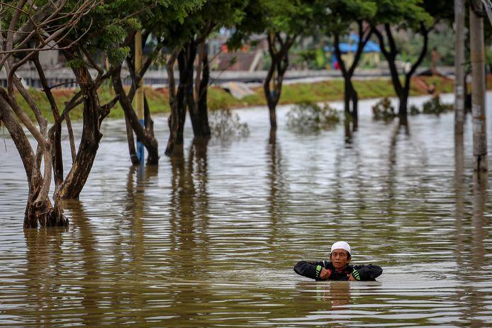 Een man waadde gisteren door het wader in Tangerang, dichtbij Jakarta. In het gebied regent het al dagen, wat zorgt voor overstromingen.