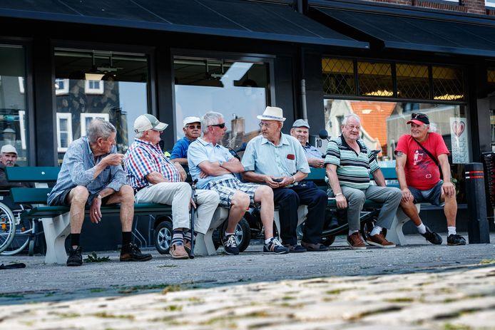 De bankjes op de Markt zitten geregeld vol met deze ouderen, die elke dag kijken hoe het centrum om hen heen verandert.