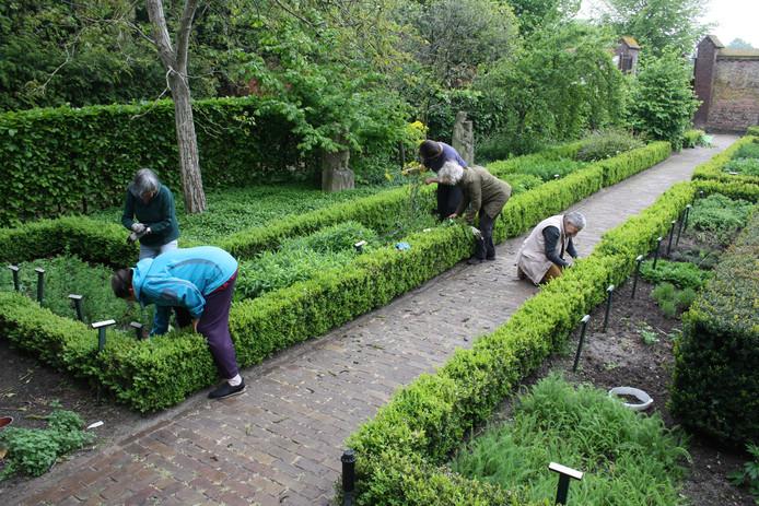 Vrijwilligers houden de kruidentuin bij van het Udense museum/abdij.