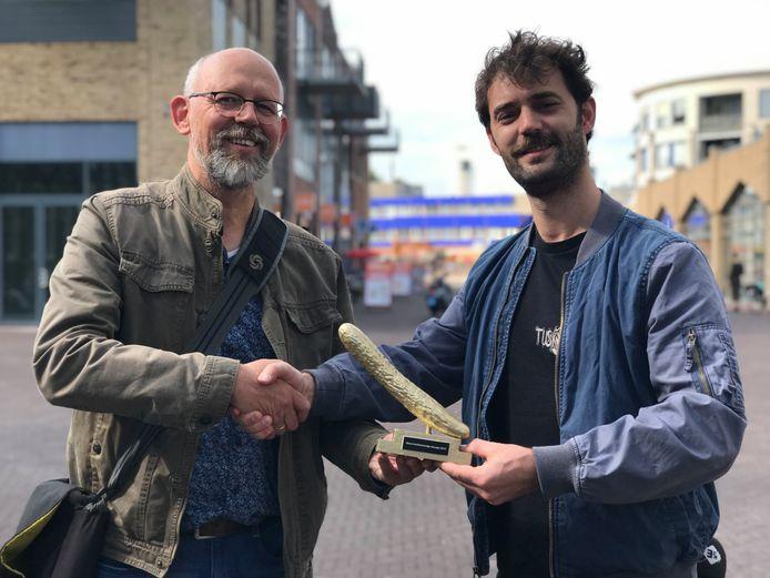 Tom van den Berg (links) ontvangt de Gouden Komkommer 2019 uit handen van presentator Herman Hofman.