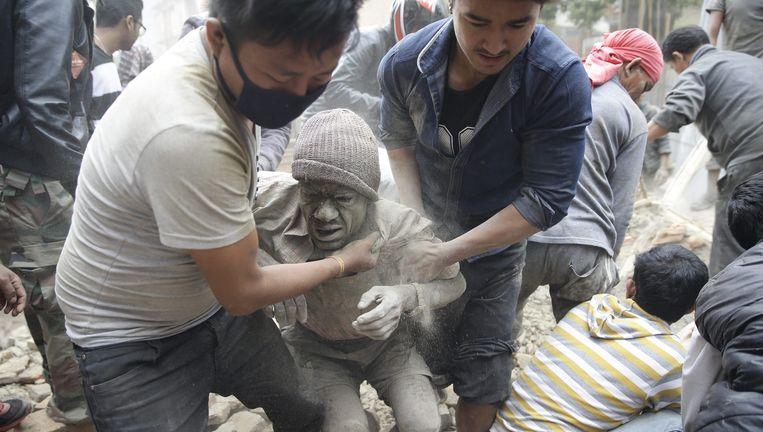 Een slachtoffer wordt in Kathmandu onder het puin van een ingestort gebouw vandaan gehaald. Beeld anp