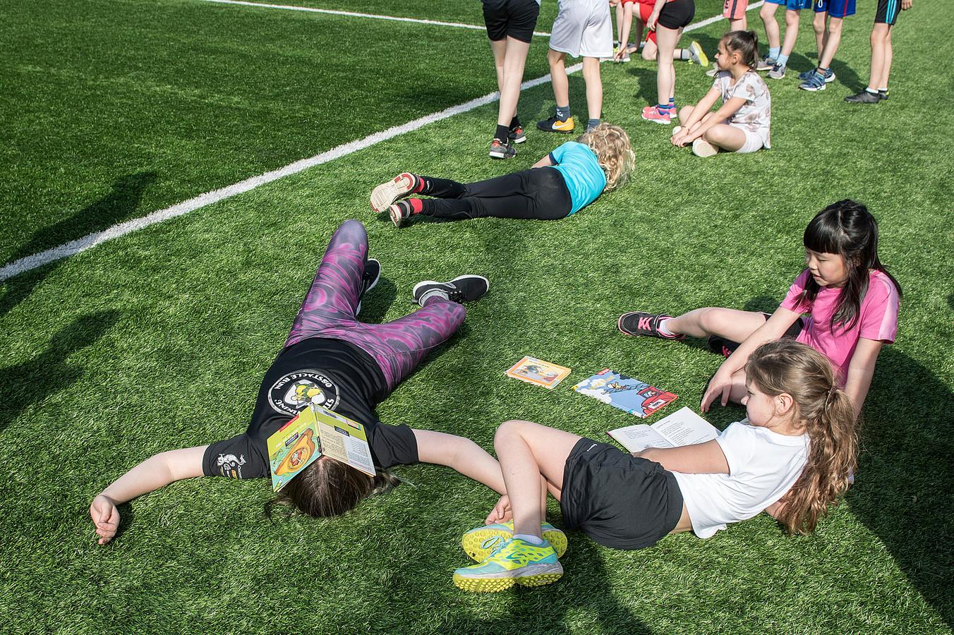 Kinderen aan de boeken tijdens de sportdag.
