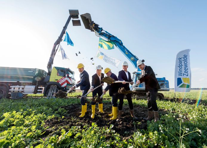 Mannen in pak verrichten de symbolische aftrap van Windpark Zeewolde. Onder hen de Flevolandse gedeputeerde Jop Fackeldey en wethouder Ewout Suithoff van Zeewolde.