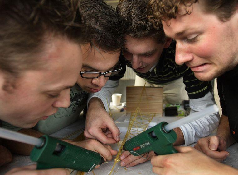 Studenten van de TU Delft in 2007 aan het werk tijdens de spaghetti-bruggenbouwwedstrijd. Daarbij moet 1 kg spaghetti worden verwerkt tot een brug met een spanwijdte van 1 meter die 1 kg gewicht moet kunnen dragen. Beeld null