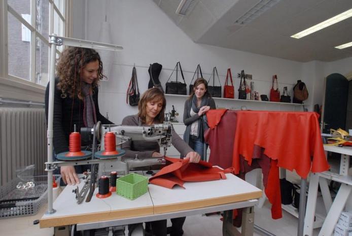 Charlotte Evers (achter de naaimachine) met stagiaires Marije Danen en Astrid Hoeken in haar leeratelier in de vroegere HBS. foto Jan Wamelink