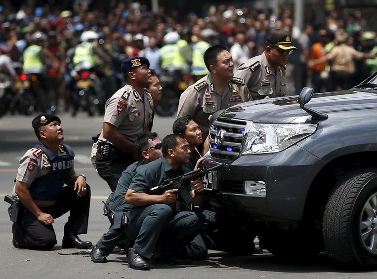 Agenten schuilen achter een auto terwijl ze zoeken naar verdachten. Beeld reuters