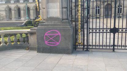 Aanhangers Extinction Rebellion brengen logo en slogans met krijtverf op koninklijk paleis aan