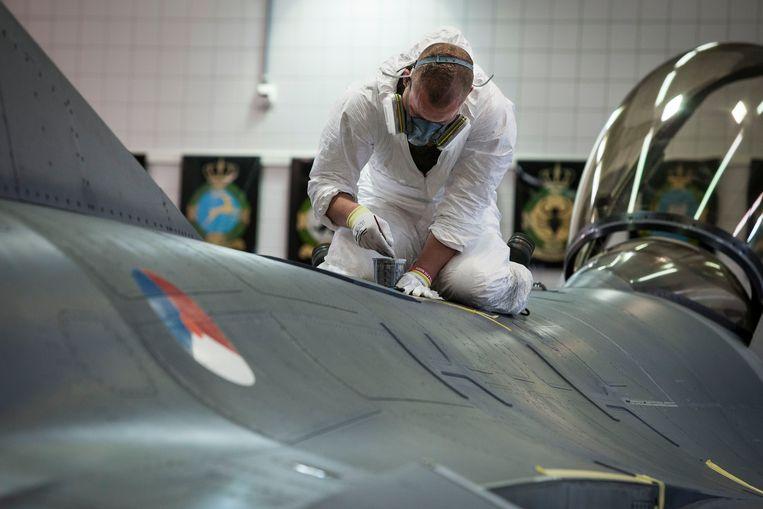 Schilderwerkzaamheden aan een F16 in Logistiek Centrum Woensdrecht. Beeld TR BEELD
