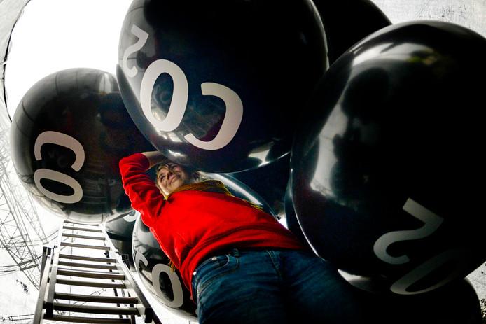 Bij de kolencentrale Neurath in het Duitse Grevenbroich houdt een milieuactivist grote ballonnen vast met daarop de tekst CO2. Op 6 november begint hier de VN-conferentie over klimaatverandering. Foto: Philipp Guelland
