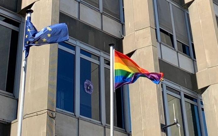 De viooltjes hangen aan de ramen van de politietoren, vlak bij de regenboogvlag.