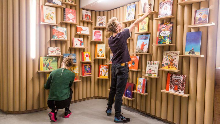 De bontgekleurde boeken zijn kriskras verspreid over de met kartonnen kokers bedekte wanden Beeld Tammy van Nerum