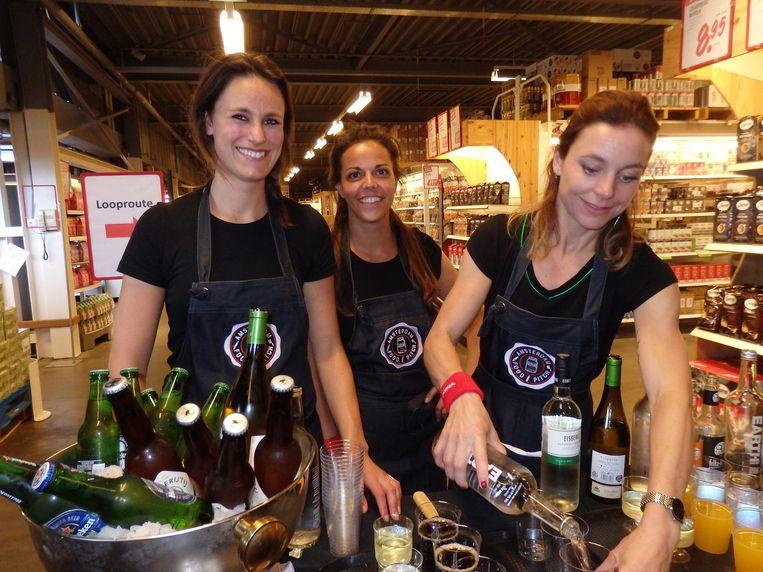 Valerie Beukeboom, Marijn Gommans en Jorit Gravemaker van De Kweker, vandaag barpersoneel tussen de schappen. Beeld Schuim