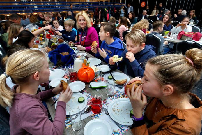 Leerlingen van cbs De Tamboerijn, in gezelschap van burgemeester Melissant (midden) laten zich de broodjes smaken.